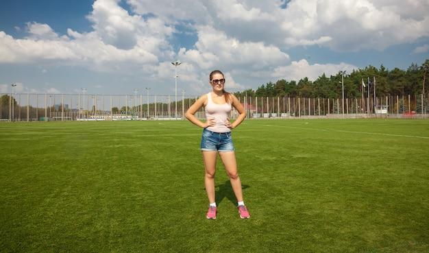 Mooie slanke vrouw staande op het voetbalveld op zonnige dag