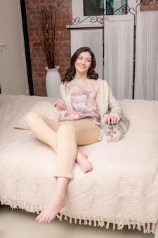 Mooie slavische brunette vrouw liggend op een bed met een bleke kat en glimlachen.