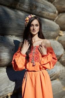Mooie slavische vrouw in een oranje etnische jurk en een krans van bloemen op haar hoofd. mooie natuurlijke make-up. portret russisch meisje
