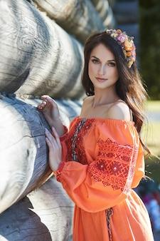 Mooie slavische vrouw in een oranje etnische jurk en een krans van bloemen op haar hoofd