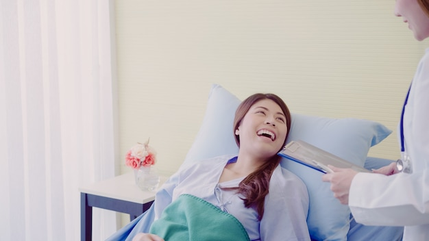 Mooie slimme aziatische arts en patiënt bespreken en iets met klembord verklaren