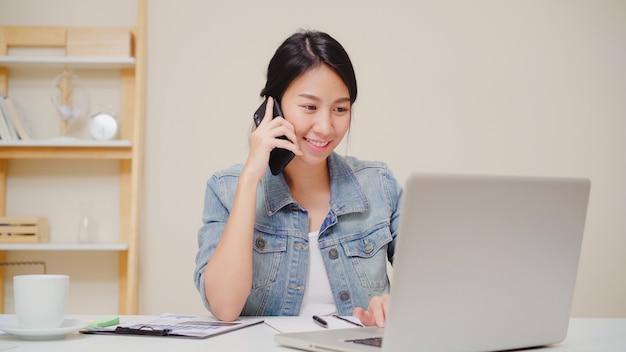 Mooie slimme bedrijfs aziatische vrouw in slimme vrijetijdskleding die aan laptop werken en op telefoon spreken terwijl het zitten op lijst in creatief bureau.