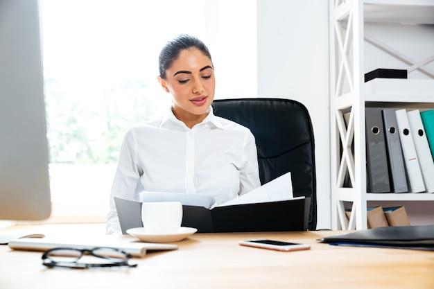 Mooie slimme zakenvrouw die naar documenten kijkt terwijl ze aan het bureau zit