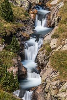 Mooie sluier draperende waterval, bemoste rotsen in de pyreneeën in spanje