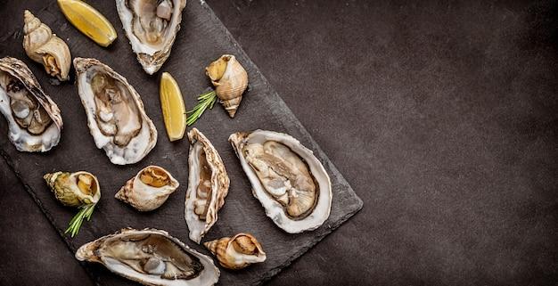Mooie smakelijke set rauwe oesters en gekookte slakken op zwarte schotel
