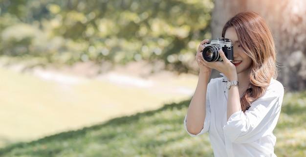 Mooie smiley aziatische vrouw met behulp van camera buitenshuis onder het zonlicht.