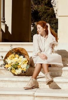Mooie smileyvrouw buitenshuis met boeket van lentebloemen