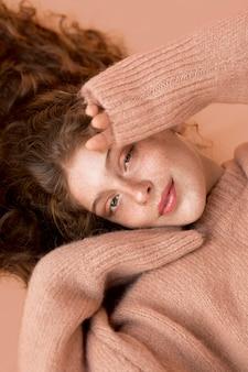 Mooie smileyvrouw die een roze sweater draagt