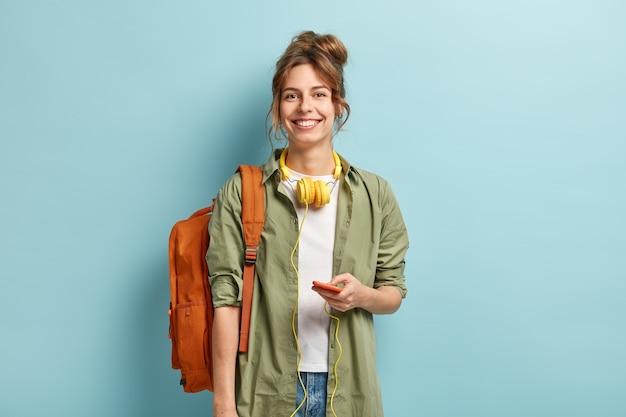 Mooie smilig vrouwelijke reiziger heeft vrije tijd, geniet van online communicatie, verbonden met een koptelefoon, luistert naar muziek uit de afspeellijst, draagt casual wit t-shirt en groen shirt, draagt rugzak