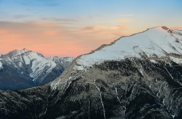 Mooie sneeuw afgetopte bergen tegen de schemeringhemel bij het nationale park van banff in alberta, canada.