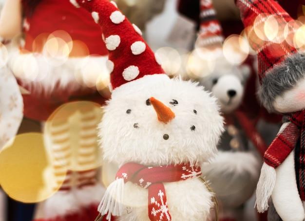 Mooie sneeuwpop speelgoed close-up. pluizige kerstspeelgoed. glimlachend sneeuwpop speelgoed in een rode hoed close-up.