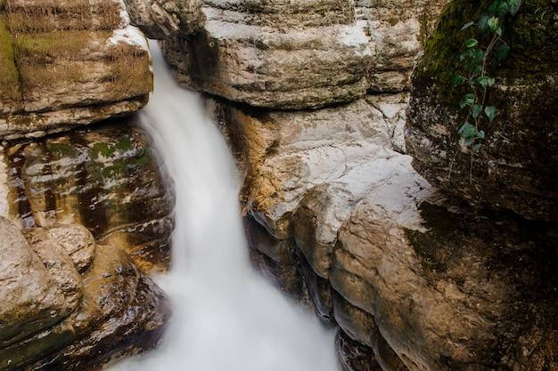 Mooie snelle watervalstroom die onder rotsen in martvili-canion op de herfstdag stroomt