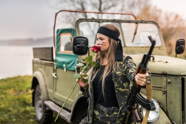 Mooie soldaat met roze bloem en geweer