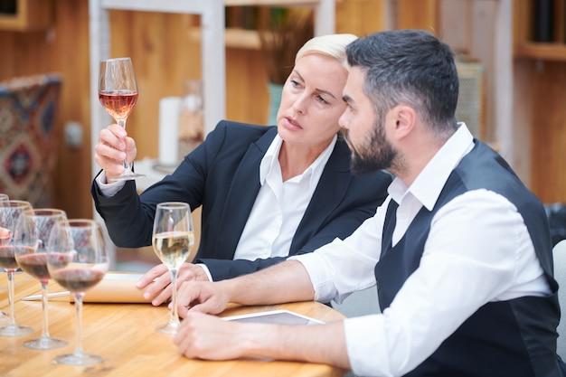 Mooie sommelier met een glas witte wijn die zijn kenmerken geeft in gesprek met collega