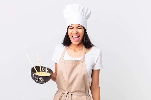 Mooie spaanse chef-kokvrouw die agressief schreeuwt, erg boos kijkt en een noedelkom vasthoudt