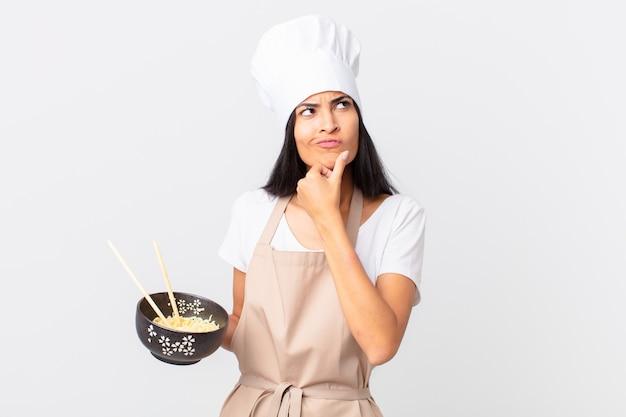 Mooie spaanse chef-kokvrouw die denkt, zich twijfelachtig en verward voelt en een noedelkom vasthoudt