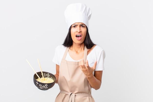 Mooie spaanse chef-kokvrouw die er wanhopig, gefrustreerd en gestrest uitziet en een noedelkom vasthoudt