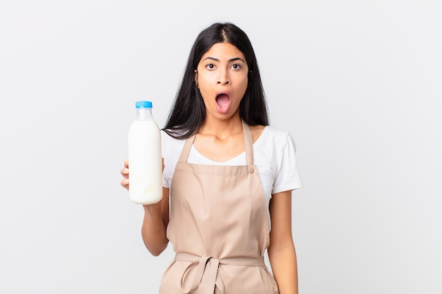 Mooie spaanse chef-kokvrouw die erg geschokt of verrast kijkt en een melkfles vasthoudt