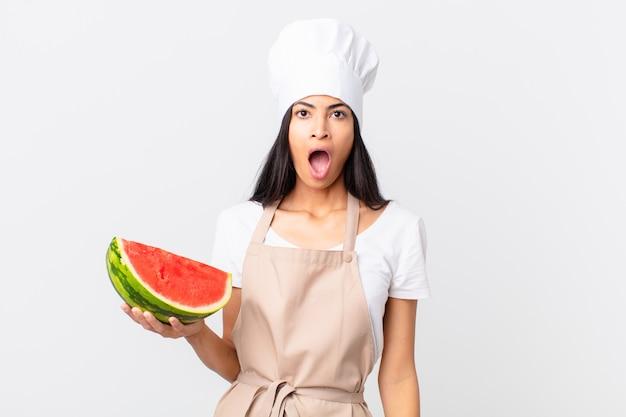 Mooie spaanse chef-kokvrouw die erg geschokt of verrast kijkt en een watermeloen vasthoudt