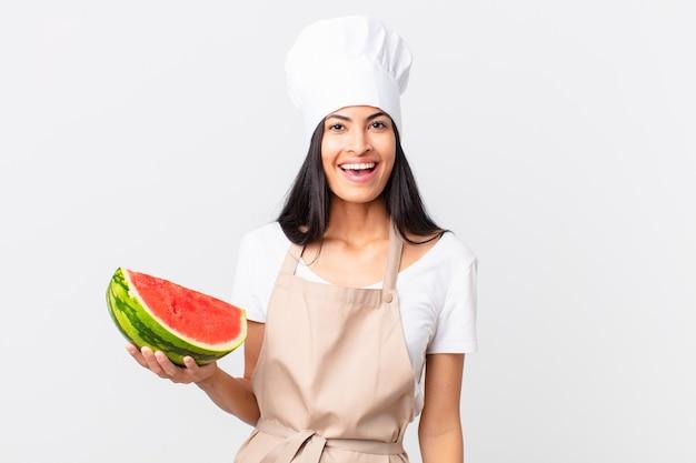 Mooie spaanse chef-kokvrouw die gelukkig en aangenaam verrast kijkt en een watermeloen vasthoudt