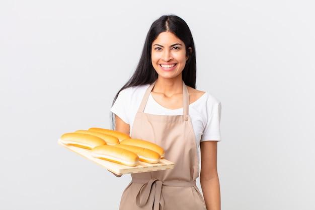 Mooie spaanse chef-kokvrouw die gelukkig glimlacht met een hand op de heup en zelfverzekerd en een dienblad met broodbroodjes vasthoudt