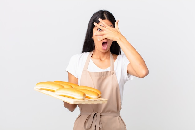 Mooie spaanse chef-kokvrouw die geschokt, bang of doodsbang kijkt, haar gezicht bedekt met de hand en een dienblad met broodbroodjes vasthoudt