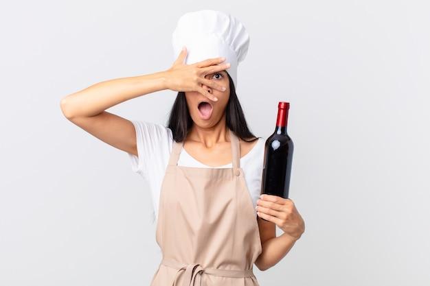 Mooie spaanse chef-kokvrouw die geschokt, bang of doodsbang kijkt, haar gezicht bedekt met de hand en een fles wijn vasthoudt