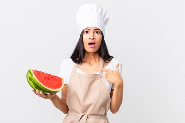 Mooie spaanse chef-kokvrouw die geschokt en verrast kijkt met wijd open mond, wijzend naar zichzelf en een watermeloen vasthoudend