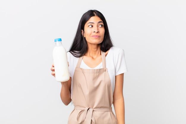 Mooie spaanse chef-kokvrouw die haar schouders ophaalt, zich verward en onzeker voelt en een melkfles vasthoudt