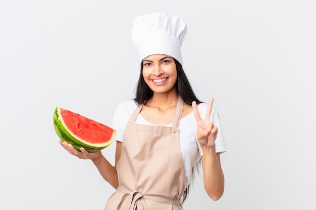 Mooie spaanse chef-kokvrouw die lacht en er gelukkig uitziet, overwinning of vrede gebaart en een watermeloen vasthoudt