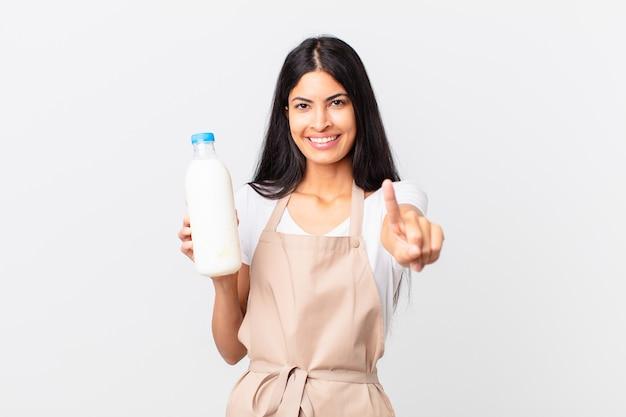 Mooie spaanse chef-kokvrouw die lacht en er vriendelijk uitziet, nummer één toont en een melkfles vasthoudt