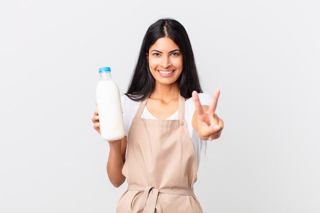 Mooie spaanse chef-kokvrouw die lacht en er vriendelijk uitziet, nummer twee toont en een melkfles vasthoudt