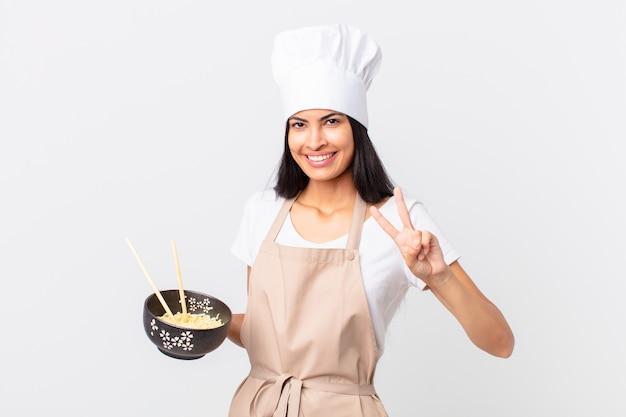 Mooie spaanse chef-kokvrouw die lacht en er vriendelijk uitziet, nummer twee toont en een noedelkom vasthoudt