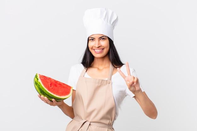 Mooie spaanse chef-kokvrouw die lacht en er vriendelijk uitziet, nummer twee toont en een watermeloen vasthoudt