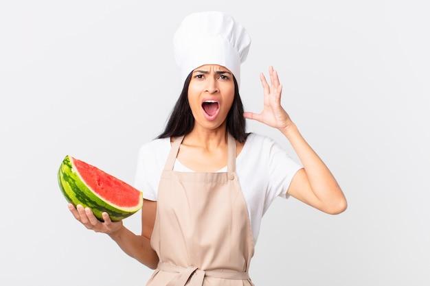 Mooie spaanse chef-kokvrouw die met handen in de lucht schreeuwt en een watermeloen vasthoudt
