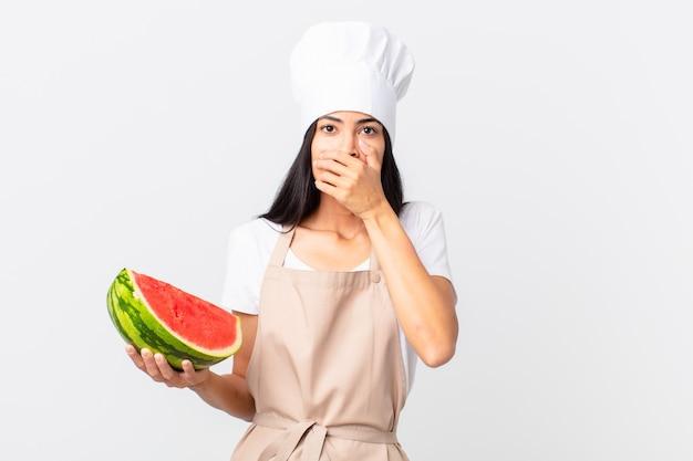 Mooie spaanse chef-kokvrouw die mond bedekt met handen met een geschokt en een watermeloen vasthoudt