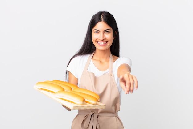 Mooie spaanse chef-kokvrouw die naar de camera wijst en jou kiest en een dienblad met broodbroodjes vasthoudt