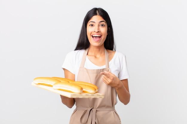 Mooie spaanse chef-kokvrouw die opgewonden en verrast kijkt en naar de zijkant wijst en een dienblad met broodbroodjes vasthoudt