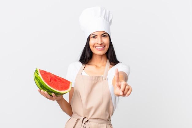 Mooie spaanse chef-kokvrouw die trots en zelfverzekerd glimlacht en nummer één maakt en een watermeloen vasthoudt