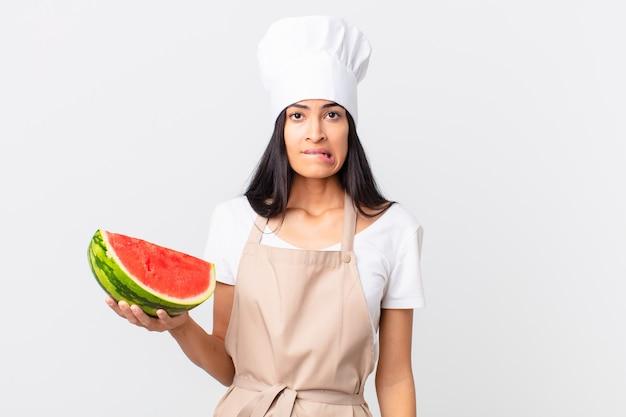 Mooie spaanse chef-kokvrouw die verbaasd en verward kijkt en een watermeloen vasthoudt