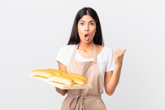 Mooie spaanse chef-kokvrouw die verbaasd in ongeloof kijkt en een dienblad met broodbroodjes vasthoudt