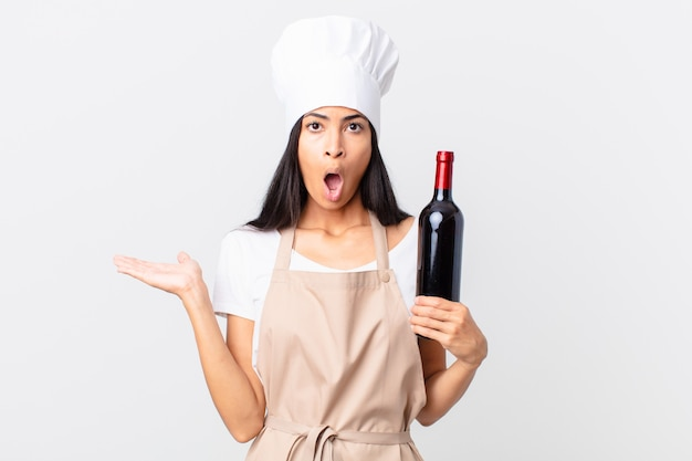 Mooie spaanse chef-kokvrouw die verrast en geschokt kijkt, met open mond terwijl ze een voorwerp vasthoudt en een fles wijn vasthoudt