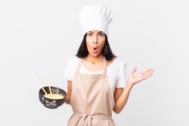 Mooie spaanse chef-kokvrouw die verrast en geschokt kijkt, met open mond terwijl ze een voorwerp vasthoudt en een noedelkom vasthoudt