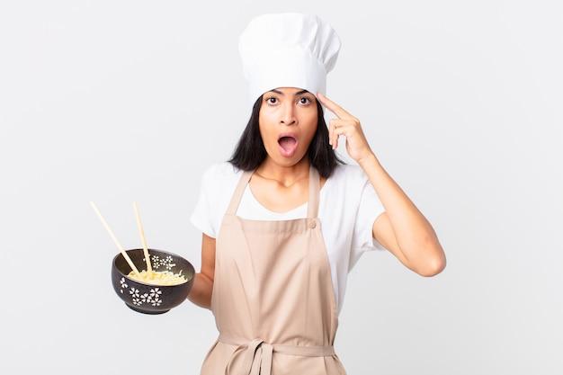 Mooie spaanse chef-kokvrouw die verrast kijkt, een nieuwe gedachte, idee of concept realiseert en een noedelkom vasthoudt