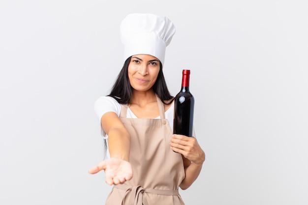 Mooie spaanse chef-kokvrouw die vrolijk lacht met vriendelijk en een concept aanbiedt en toont en een fles wijn vasthoudt