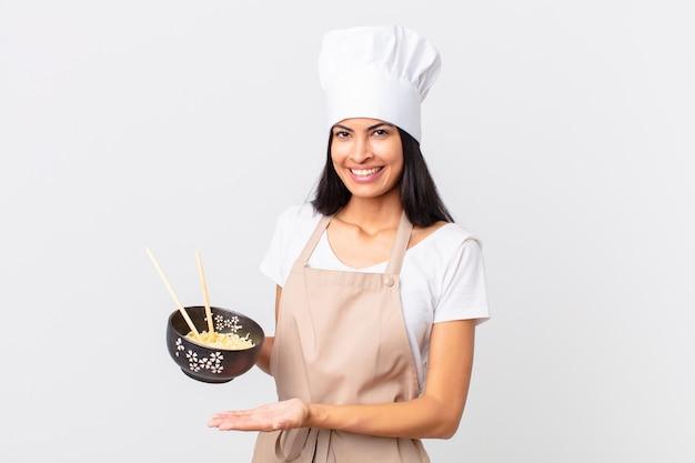 Mooie spaanse chef-kokvrouw die vrolijk lacht, zich gelukkig voelt en een concept toont en een noedelkom vasthoudt