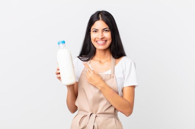 Mooie spaanse chef-kokvrouw die vrolijk lacht, zich gelukkig voelt en naar de zijkant wijst en een melkfles vasthoudt