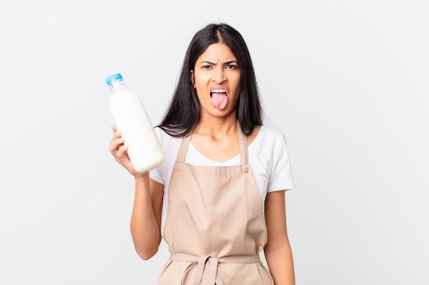 Mooie spaanse chef-kokvrouw die walgt en geïrriteerd voelt en tong uitsteekt en een melkfles vasthoudt