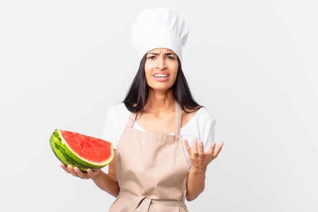 Mooie spaanse chef-kokvrouw die wanhopig, gefrustreerd en gestrest kijkt en een watermeloen vasthoudt