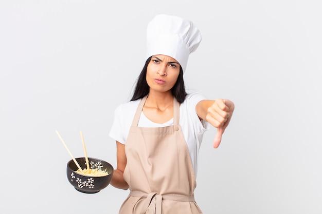 Mooie spaanse chef-kokvrouw die zich boos voelt, duimen naar beneden laat zien en een noedelkom vasthoudt